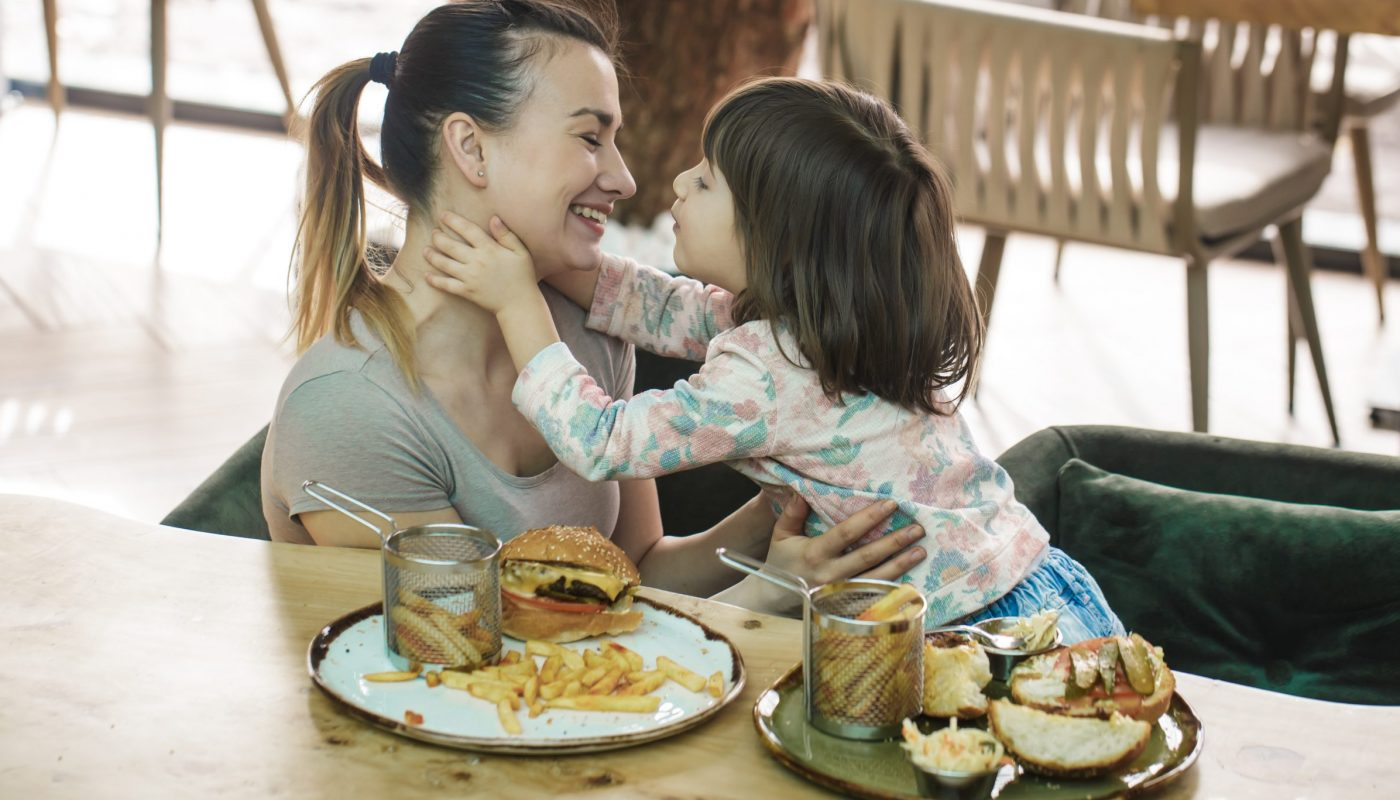 Loving family. Mom with cute daughter eating fast food in a cafe, family and nutrition concept